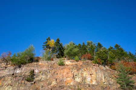 A sheer rock face with trees atop the ridge line against blue sky  Stock Photo - 16953349