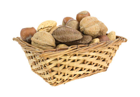 A small wicker basket filled with an assortment of whole nuts on a white background  Stock Photo - 17094071