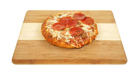 A freshly cooked personal size thick pan pizza on a wood cutting board