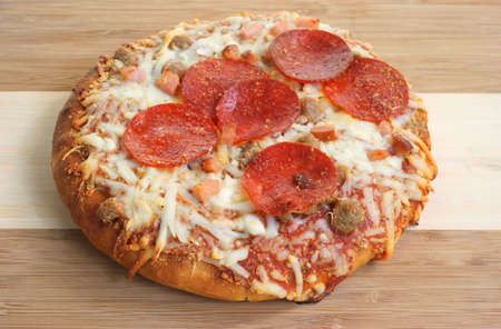 A small single serving thick crust meat pizza on a wood cutting board