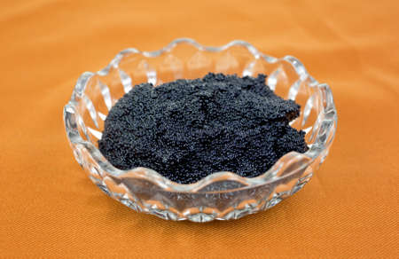 A small glass bowl filled with black caviar on a cloth background