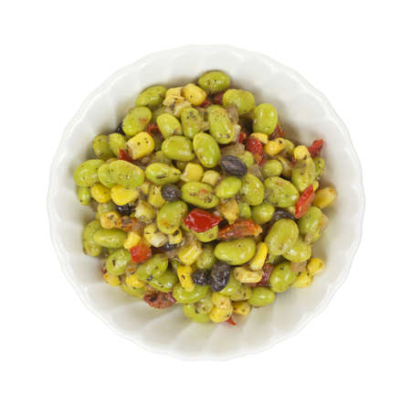 Top view of a small white bowl filled with a small serving of edamame salad  photo