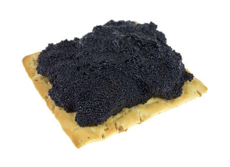 A wheat cracker with caviar on a white background
