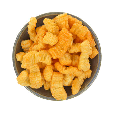 stoneware: An old stoneware bowl filled with crispy crunchy cheddar cheese snacks on a white background