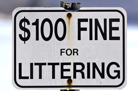littering: Close view of an old fine for littering sign with bent top and worn metal post outdoors