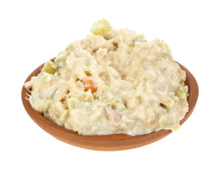 A small bowl filled with fresh tuna salad on a white background