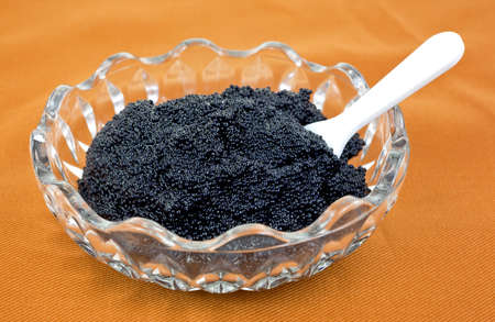 A small glass bowl filled with black caviar with a small white plastic spoon inserted into the caviar on a cloth background