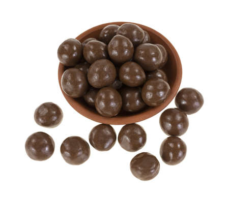 A small dish filled to overflowing with milk chocolate balls on a white background  Stock Photo