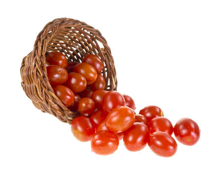 Several small grape tomatoes spilling from a wicker basket onto a white background Stock Photo - 17954044