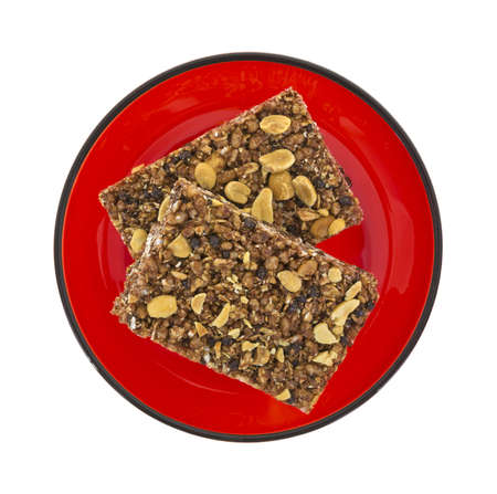 Top view of two cocoa honey and peanut granola bars on a red plate  photo