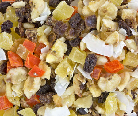 A very close view of a healthy snack mix of coconut, papaya, bananas, pineapple, raisins and dates