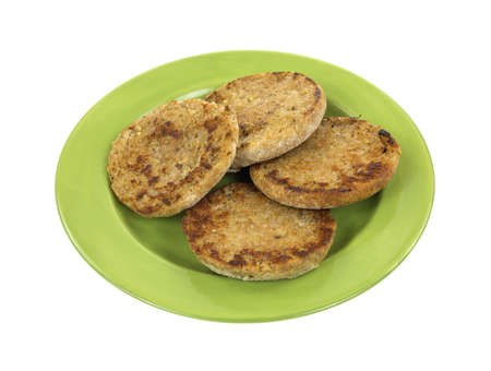 green been: Four halves of English muffins that have been cooked on a green plate