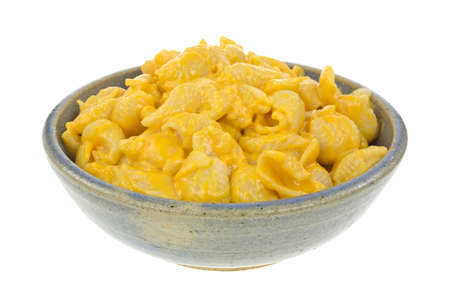 stoneware: An old stoneware bowl filled with pasta shells in cheese sauce on a white background.