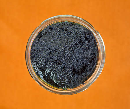 Top view of a jar of just opened black caviar on a cloth background.