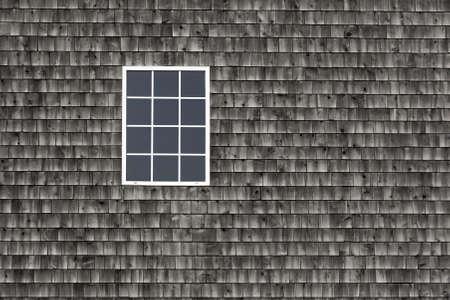A single window set against weathered cedar shingles.