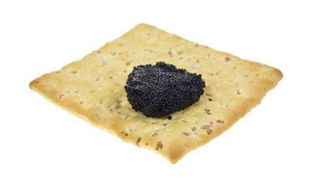 A stone ground wheat cracker with a small portion of black caviar on a white background. Stock Photo