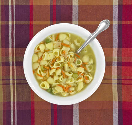 Top view of a bowl of chicken broth soup with pasta and vegetables in a white bowl with spoon on a colorful tablecloth background. photo