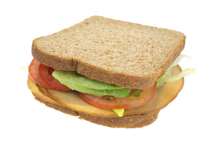 A whole wheat sandwich with tofu smoked turkey tomatoes and lettuce. Stock Photo