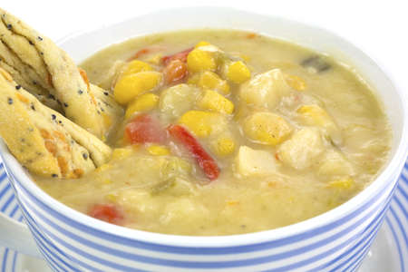 chowder: A very close view of corn, potato and red pepper chowder with twisted crackers in cup.
