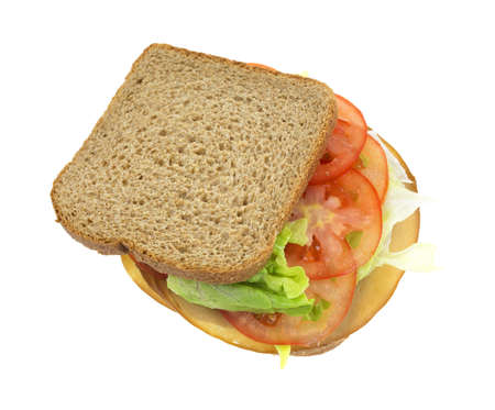 A sandwich of whole wheat bread with lettuce tomatoes and tofu meatless turkey on a white background.