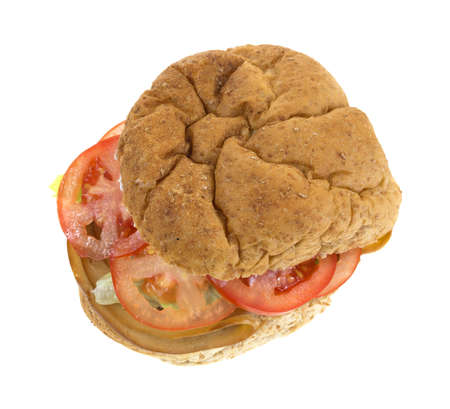 A sandwich made of smoked tofu turkey with lettuce and tomatoes on a whole wheat bulky roll. Stock Photo