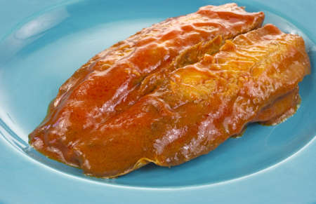 A fillet of smoked herring covered with tomato sauce on a blue plate.