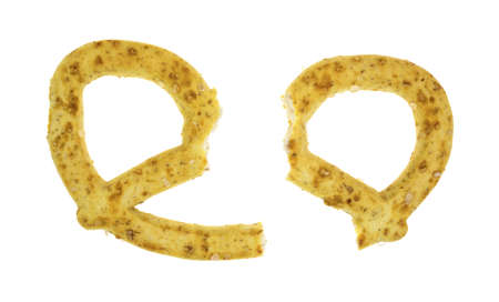 A single honey and oat flavored pretzel broken on a white background.
