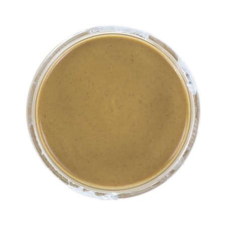 Bovenaanzicht van een geopend, maar ongebruikt pot pindakaas op een witte achtergrond.