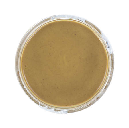 Top view of an opened but unused jar of peanut butter on a white background. Standard-Bild