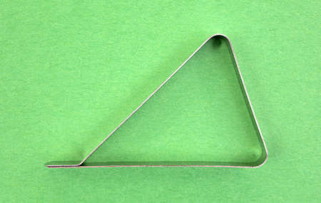 A single stainless steel tablecloth clamp used for keeping tablecloths from blowing from picnic tables on a green background.