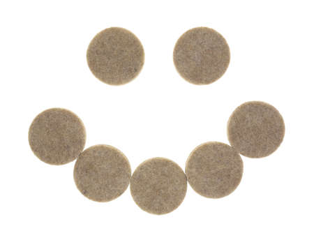 A group of felt surface protectors for protecting furniture and flooring in the shape of a smile on a white background.