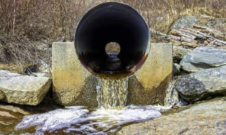 runoff: An old rusted metal culvert with water runoff.