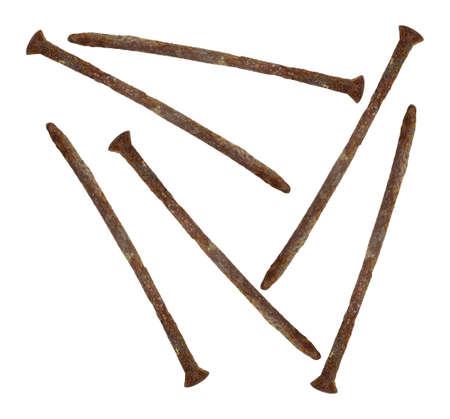 Several old rusty spikes on a white background.
