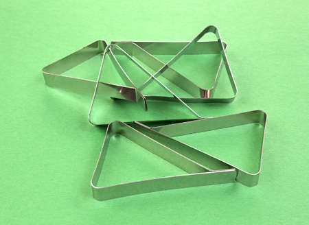A group of stainless steel tablecloth clamps used for keeping tablecloths from blowing from picnic tables on a green background.