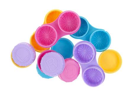 revoltijo: Un revoltijo de varios estuches de lentes de contacto con las cubiertas por separado sobre un fondo blanco. Foto de archivo