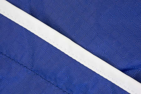 Close view of blue nylon fabric with a bright white stripe at an angle.