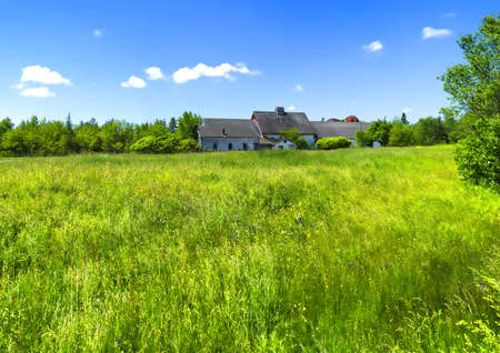 Distant view of a deserted farmhouse with lush green field in the foreground. photo