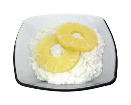 A large serving of large curd cottage cheese with two sliced of pineapple on a white background. Stock Photo - 20721804