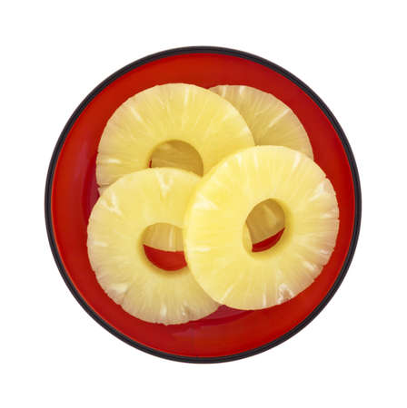Top view of a red dish with several cored pineapple rings on a white background. Stock Photo - 20721815