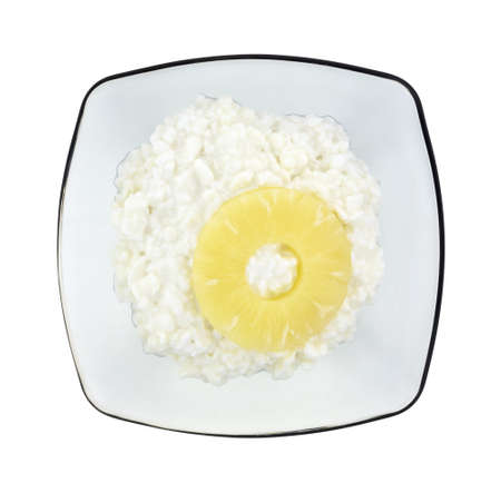 Top view of a translucent gray bowl with a serving of cottage cheese and a single slice of pineapple on a white background. Stock Photo - 20910801