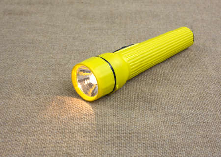 A small yellow flashlight with the lamp on atop a burlap cloth. Banco de Imagens - 20912054