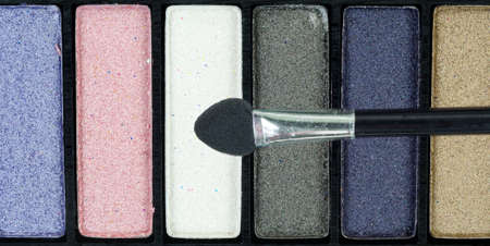 Top view of several shades of eye shadow with a small brush. Stok Fotoğraf