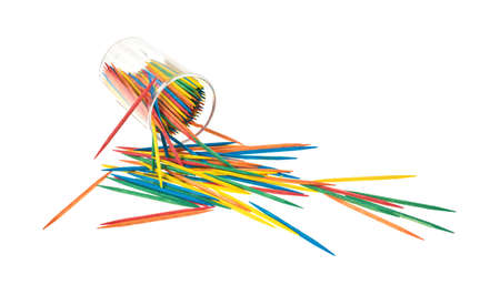 A plastic container spilling colorful toothpicks on to a white background. photo