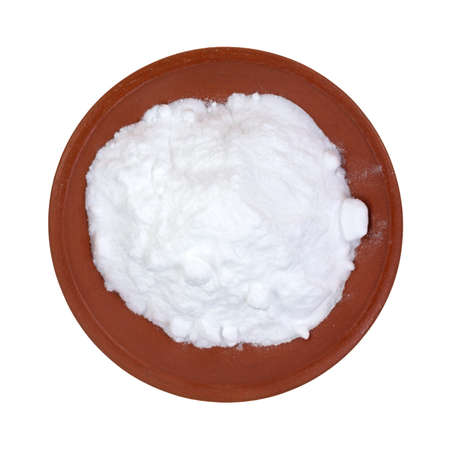 Top view of baking soda in a red clay bowl on a white background
