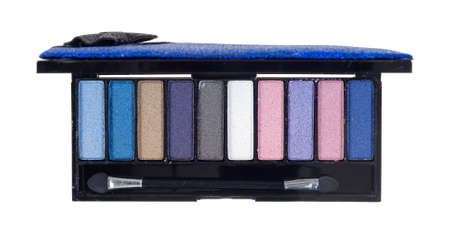 A small cosmetic case with several shades of eye shadow and a small brush on a white background  photo