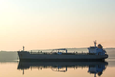 A large cargo ship back-lit by the early morning light as it goes to port
