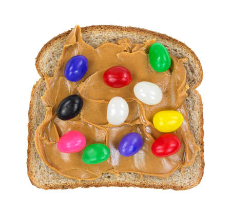 A slice of whole wheat bread with peanut butter and jelly beans on a white background.  photo