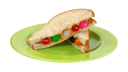 A peanut butter with jelly beans cut in half on a green plate. photo