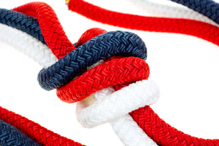 A very close view of  red white and blue rope in a tight knot on a white background. Stock Photo