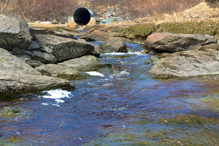 culvert: A stream surrounded by barnacle covered rocks with a distant old culvert at low tide  Stock Photo